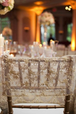 Golden chair with an embroidered and beaded sleeve at a wedding reception