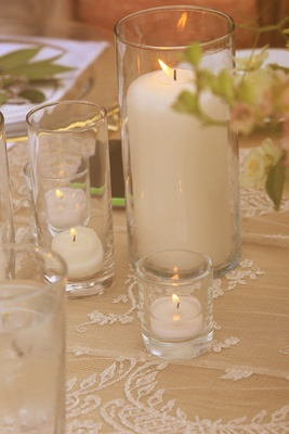 votive candles and pillar candle in hurricanes on lace tablecloth, wedding