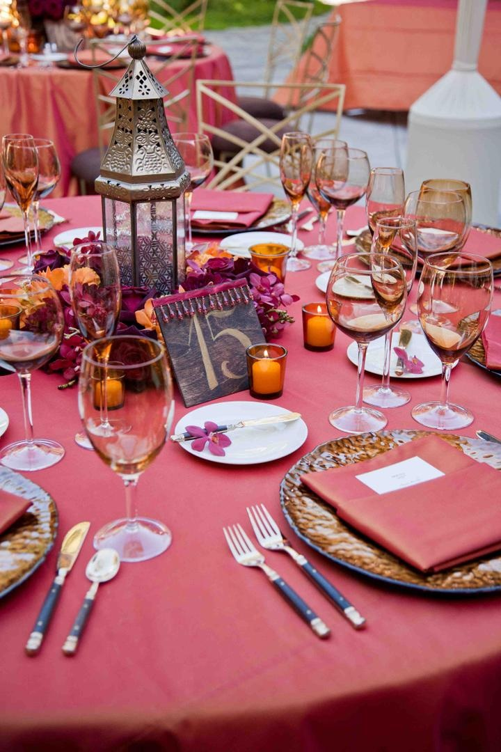 Wedding reception table with red tablecloth and napkin, amber glassware, and earth-toned chargers
