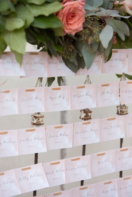 Wedding reception escort card pink watercolor design printed calligraphy on strands of leather