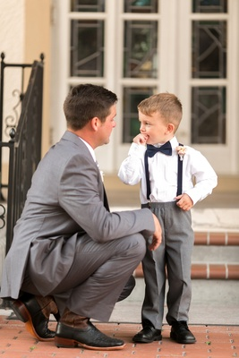 Groom in grey suit and black shoes talks to to ring bearer in grey pants, navy suspenders & bow tie