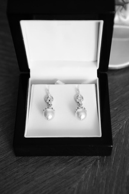 Black and white photo of diamond pearl earrings in jewelry box
