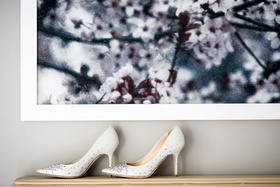 White pumps with rhinestones crystals jimmy choo on shelf with artwork on wall