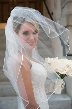 Bride in a veil and spaghetti strap dress with embroidered bodice holds bouquet of white flowers
