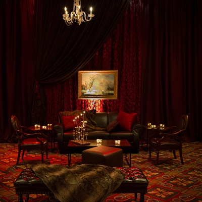 Black tufted furniture, red pillows, and fur blankets