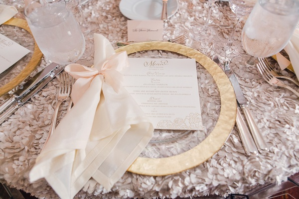 Wedding reception with textured linen flower gold charger plate white napkin with light pink bow
