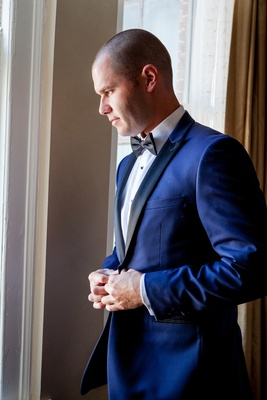 groom buttons navy tuxedo with black lapels and bow tie