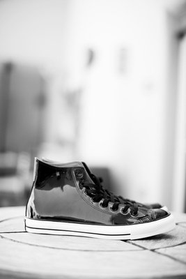 Black and white photo of leather Converse shoes