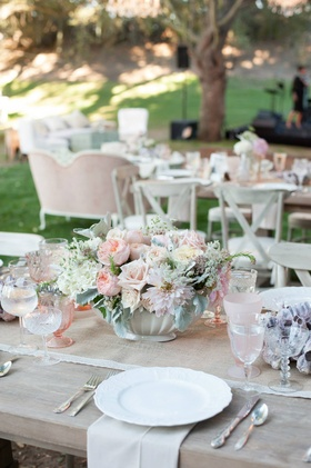 Wood table with burlap runner and blush wedding centerpiece