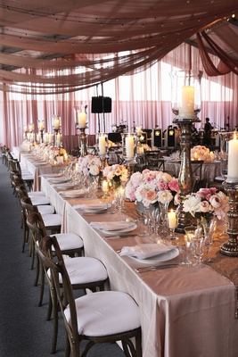 Long rectangular wedding reception table with drapes on ceiling