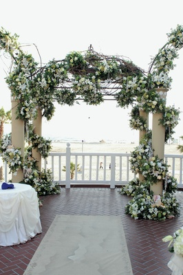 chuppah made of vines of white flowers overlooking ocean