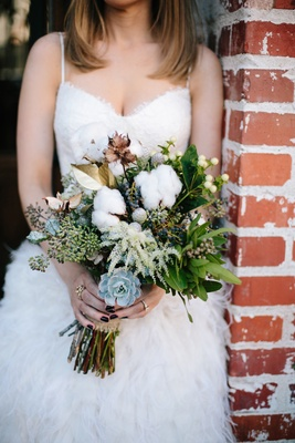 Wedding bouquet with succulents, gold leaves, and fresh cotton