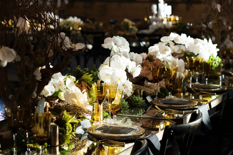Mirror reception table with white orchids, colored amber glassware, honeycomb, driftwood, greenery