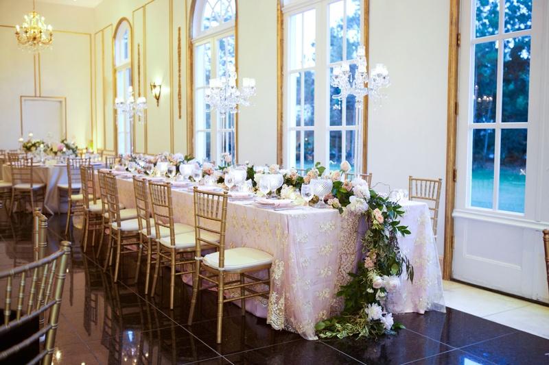 Wedding reception gold chairs blush linens long table flower runner on floor gold details ballroom