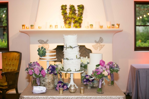 three wedding cakes with green and gold accents on table with pink and purple floral arrangements
