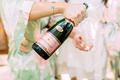 wedding getting ready photos pink green robes champagne into stemless flutes while getting ready