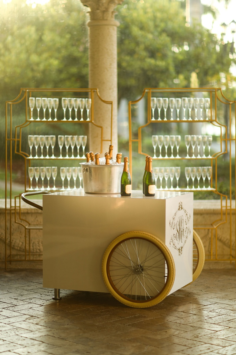 wedding reception cocktail hour vintage style champagne bar cart with couple monogram ice bucket