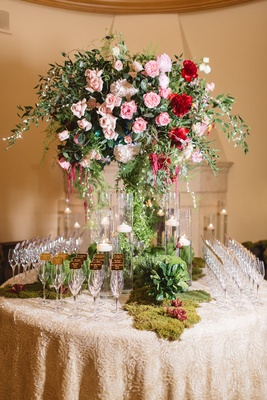 champagne glass escort cards floral table pink red flowers moss candles patterned linen