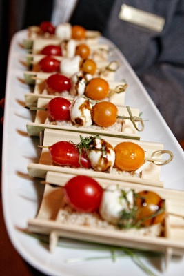 Wedding appetizer on wood display with cherry tomato and mozzarella