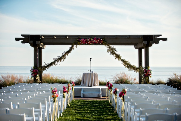 Rustic wood arbor at wedding ceremony with garland and pink flowers