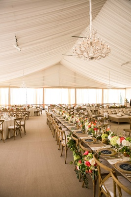 Tent wedding at Villa Bianco in Texas with chandelier, rustic tables, and green centerpieces