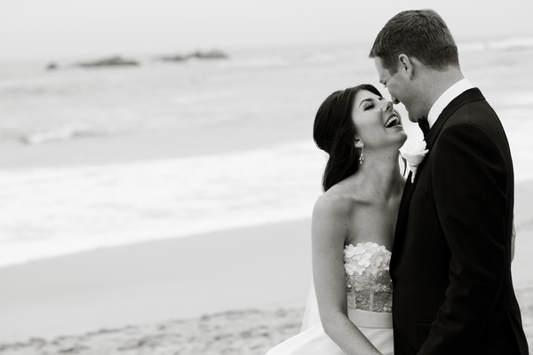 Black and white photo of couple laughing on beach