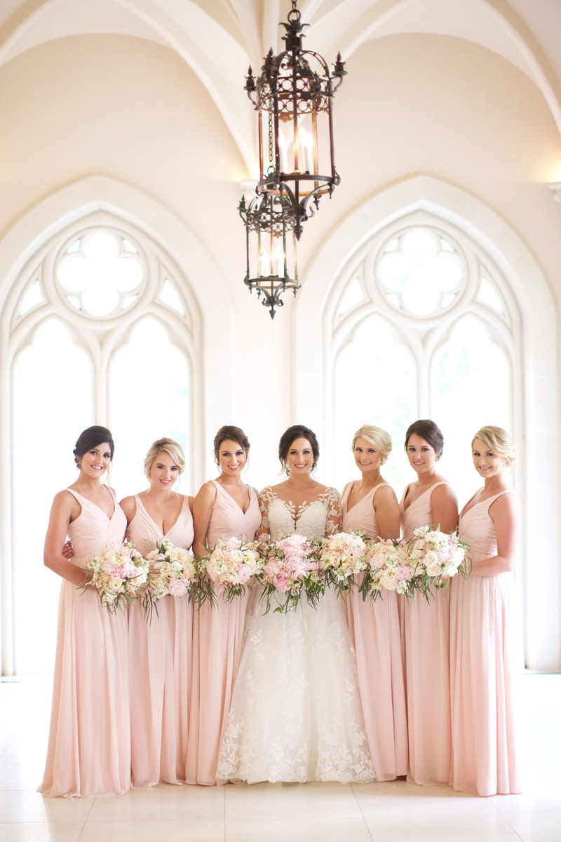 Bride in illusion long sleeve wedding dress with bridesmaids in pink long dresses v neck flowers