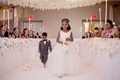 wedding ceremony white flowers on side of aisle flower girl tossing pink petals white basket