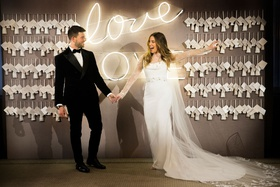 bride and groom in front of escort card walll with neon sign love in cursive lettering