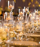 glowing reception table with floating candles in glasses among wine glasses