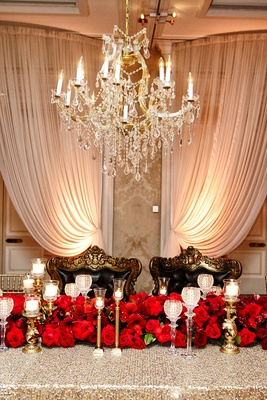 regal sweetheart table, red rose runner, candlesticks, black cushioned chair with ornate gold border