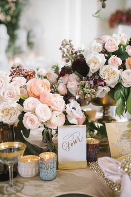 gold calligraphed table numbers at garden tablescape with ranunculus rose and anemone flowers