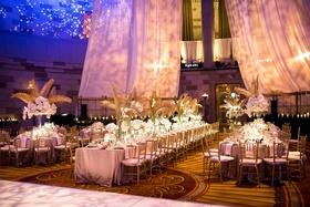 wedding reception long round table gold palm leaves drapery blue lighting dance floor ballroom