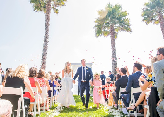 bride and groom walking up aisle with flower girl and groom daughter step-daughter flower petal toss