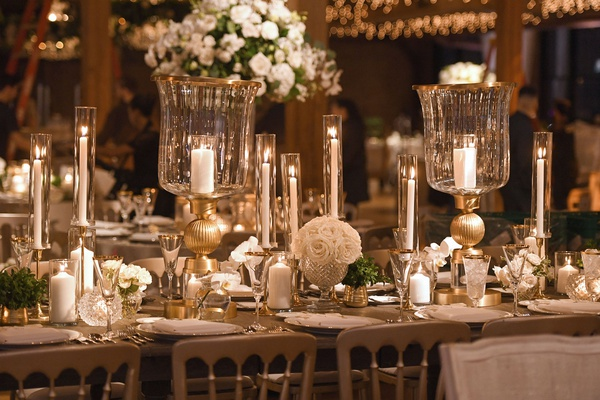 wedding reception table white flowers taper candles votive candle white rose globe vase