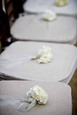 small bundles of white hydrangeas placed on each chair cushion
