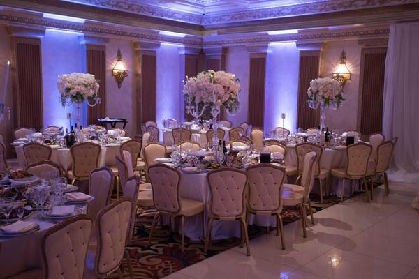 Tufted wedding event chairs banquet hall violet uplighting candelabra centerpiece white pink flowers