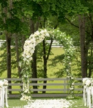 Flower petals on grass lawn aisle at outdoor ceremony farm with arch greenery white flowers