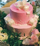 Two layer pink cake with white fondant bows
