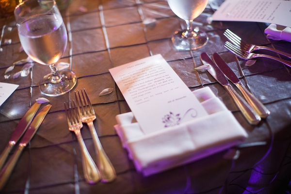 Wedding reception table with a personalized note in napkin