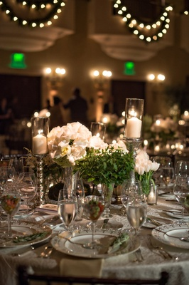 centerpieces with white roses, greenery, and candles