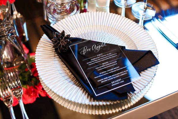 white ridged charger plate, black napkin and jeweled napkin ring, lucite menu