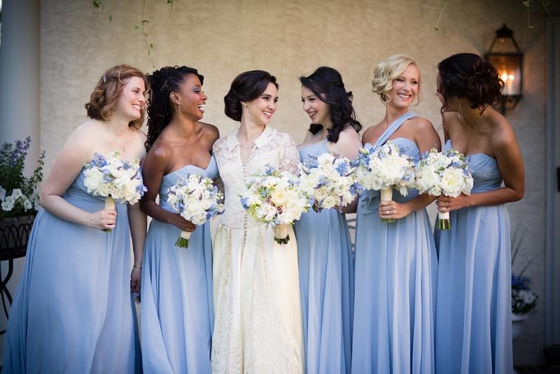 bride in vintage dress and bridesmaids wearing light blue dresses