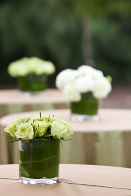 glass vase filled with green leaves topped with white roses