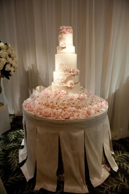 White seven layer cake with fresh pink flowers
