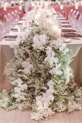wedding reception floral runner with baby's breath and orchids, neutral linens