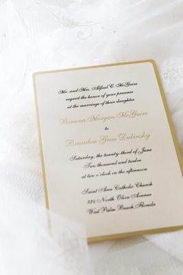 ivory invite with black calligraphy and gold border