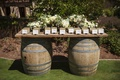 Ranch wedding reception with place card table composed of two barrels and wood board, white flowers