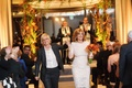 Lori Wolf in bridal suit walking down aisle with Carol Leifer in white lace dress orange bouquet