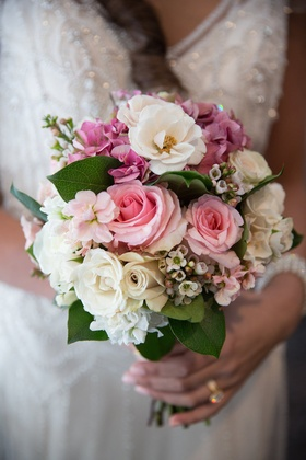 Bride holding wedding bouquet with pink rose, white rose, pink hydrangea and leaves